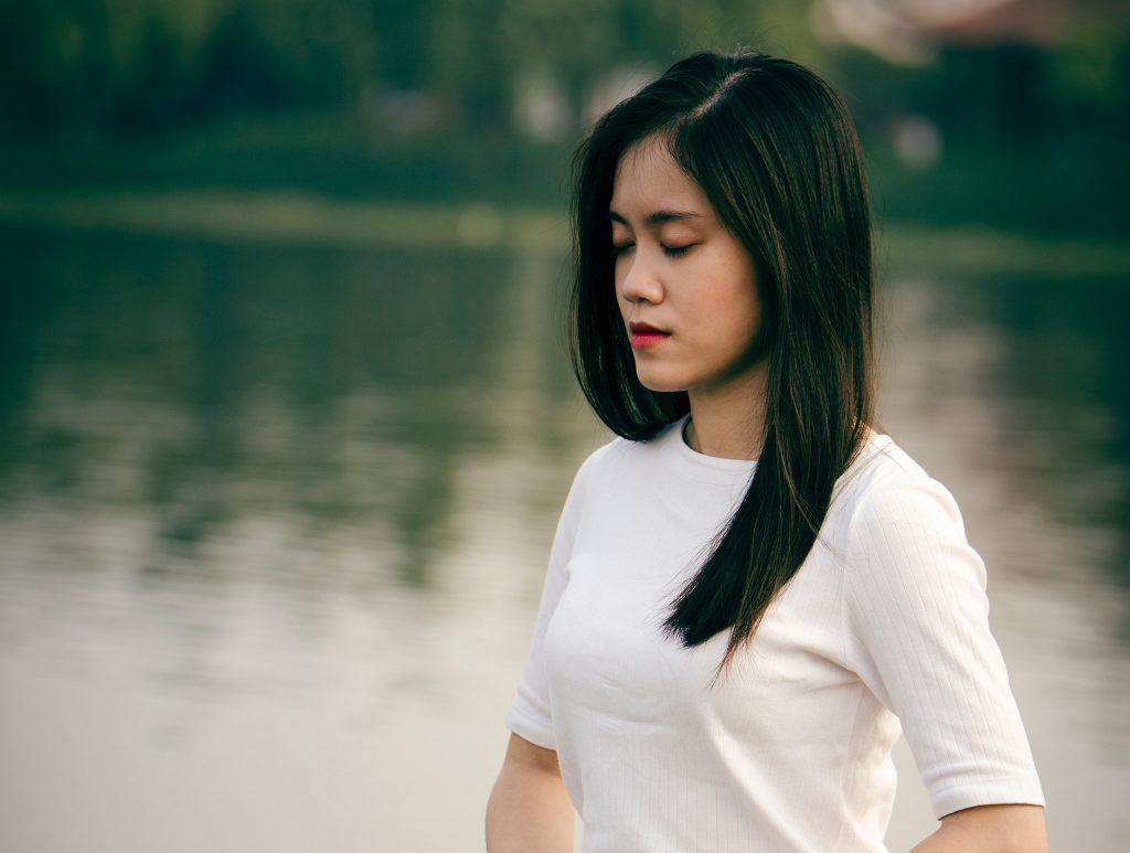 woman meditate still lake