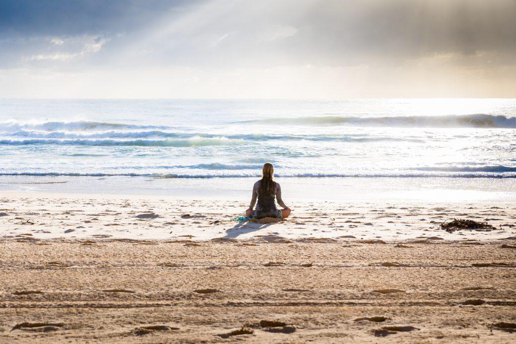 woman meditate beach
